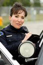 Female police officer writes ticket standing next to her patrol car Royalty Free Stock Photography