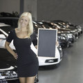 Female posing with sign in front of new cars young blond smiling holding board at a car dealership Royalty Free Stock Images