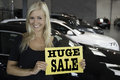 Female posing with sign in front of new cars young blond smiling holding huge sale text at a cardealership Royalty Free Stock Image