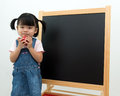 Female preschooler with apple in hand portrait of little girl holding front of the blackboard Royalty Free Stock Photos