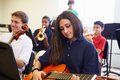 Female pupil playing guitar in high school orchestra sitting down on chair with other students Stock Photo