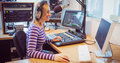 Female radio host broadcasting through microphone Royalty Free Stock Photo
