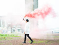 Female in raincoat with smoke bomb walking and holding a Stock Photos