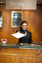 Female receptionist handing over check-out papers Royalty Free Stock Images