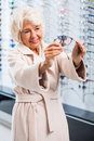 Female retiree choosing new spectacles Royalty Free Stock Photo