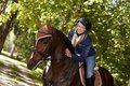 Female rider caressing horse attractive while riding in the woods Stock Photo