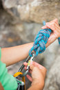 Female rock climber adjusting her harness by the face Royalty Free Stock Images
