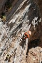 Female rock climber on handholds on challenging route on cliff Royalty Free Stock Photo