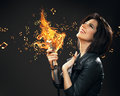 Female rock musician handing burning mic half length portrait of keeping on grey background Stock Images