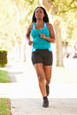 Female runner exercising on suburban street running towards camera Royalty Free Stock Image