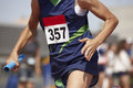 Female runner finalizing a relay race in a running track Royalty Free Stock Photo