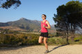 Female runner in full stride on a mountain trail summer Stock Photos