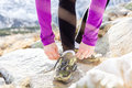 Female runner tying sports shoe in mountains on trail young woman running winter fall sunny day sport and exercising outdoors Royalty Free Stock Images