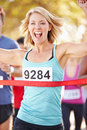 Female runner winning marathon celibrating as she wins Stock Photography