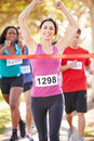 Female runner winning marathon celobrating as she wins Royalty Free Stock Images