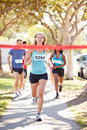 Female runner winning marathon running towards camera Royalty Free Stock Photo