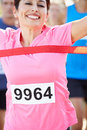 Female runner winning marathon smiling as she wins Royalty Free Stock Photography