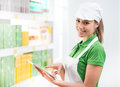 Female sales clerk with tablet at supermarket smiling holding a digital Stock Photo
