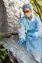 Female sanitary inspector takes a sample of water from urban wastewater Royalty Free Stock Photo