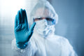 Female scientist in protective hazmat suit with hand raised Royalty Free Stock Photo