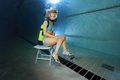 Female scuba diver take a seat underwater Royalty Free Stock Photos