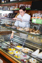 Female seller assisting in choosing dessert