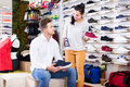 Female seller demonstrating sneakers to customer in sports store