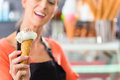 Female seller in parlor with ice cream cone young saleswoman an cornet Stock Photo
