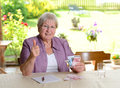 Female senior calculating her budget older woman and keeping up the thumb Royalty Free Stock Images