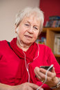 Female senior is listen musik with a smartphone Stock Image