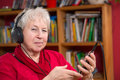 Female senior is listen musik with a smartphone Royalty Free Stock Photos