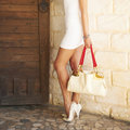 Female shod white high heel shoes holding in a hand fashion bag. Royalty Free Stock Photo