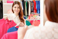 Female shopper looks at the mirror bright colors in trend young smiling brunette trying blue and red shirts looking in fashionable Royalty Free Stock Photos