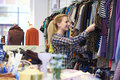 Female shopper in thrift store looking at clothes looks Royalty Free Stock Photo