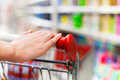 Female shopper with trolley at supermarket closeup of the hand of on the Stock Photography