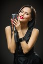 Female singer with closed eyes handing mic half length portrait of wearing black evening dress and keeping mike on grey background Stock Photos