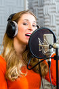 Female singer or musician for recording in studio young with microphone and headphone audio the Royalty Free Stock Image