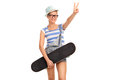 Female skater making peace hand sign studio shot of a young holding a skateboard and gesture isolated on white background Royalty Free Stock Images