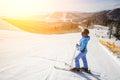 Female skier on the middle of ski slope against ski-lift Royalty Free Stock Photo
