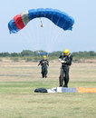 Female skydiver making safe landing on grass with open brightly Royalty Free Stock Photo