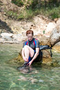 Female snorkeler young sat on a rock in the sea preparing to go snorkeling Royalty Free Stock Images