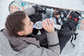 Female snowboarder is drinking for quenching the thirst resting on a snowy ground while she water caused by exhausting Royalty Free Stock Photography