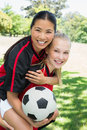 Female soccer player piggybacking teammate portrait of happy at park Royalty Free Stock Photography