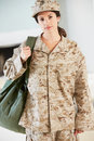 Female soldier with kit bag home for leave smiling to camera Stock Images
