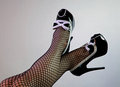 Female spectator pumps these black and white are being modeled by a who is also wearing black fish net stockings the shoes feature Stock Image