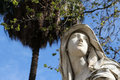 Female statue representing the glory detailed view of face of a blurred trees in background carved by marabitti palermo Stock Image