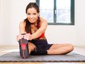 Female stretching in the gym photo of a beautiful on floor sitting on a mat Royalty Free Stock Photography