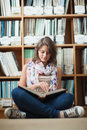Female student against bookshelf reading a book on the library floor full length of sitting and Royalty Free Stock Photo