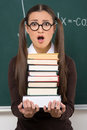 Female student with books shocked young woman holding a stack of while standing in front of the blackboard Royalty Free Stock Image