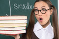 Female student with books shocked young woman holding a stack of while standing in front of the blackboard Royalty Free Stock Images